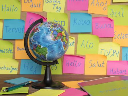 A globe in front of post it notes saying hello in multiple languages